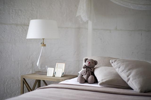 postel s medvídkem a noční stolek