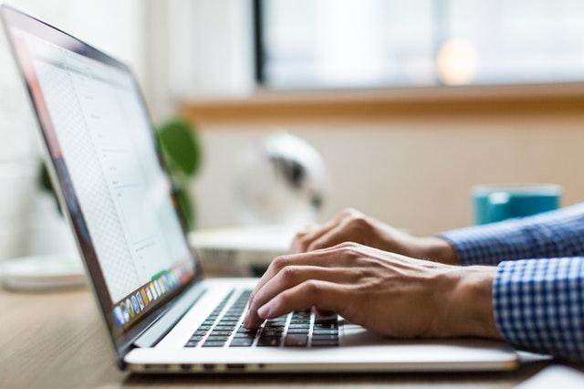 muž pracující na notebooku – detail rukou na klávesnici