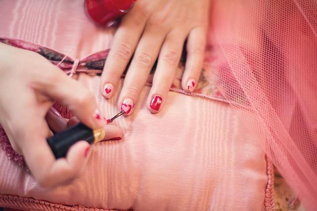lakování nehtů na růžovém pozadí