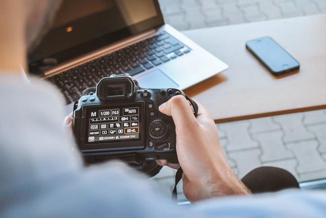 fotoaparát, někdo jej drží v ruce a mačká tlačítka, vedle je notebook