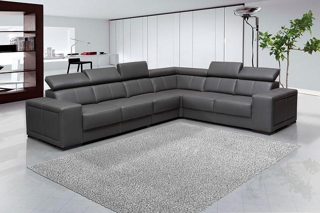 černá pohovka a šedý koberec